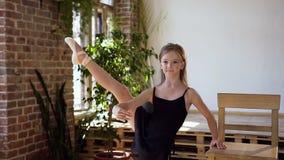 A menina de encantamento no tutu preto executa o elemento do exercício do balé clássico no salão de baile Uma bailarina bonita no filme