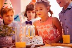 Menina de encantamento que olha seu bolo de aniversário fotos de stock