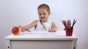 A menina de encantamento tira no álbum com um lápis em um bom humor vídeos de arquivo