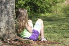 Menina de encontro à árvore fotos de stock royalty free