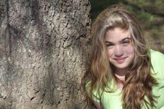 Menina de encontro à árvore Fotos de Stock