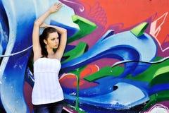 Menina de encontro à parede dos grafittis Imagens de Stock