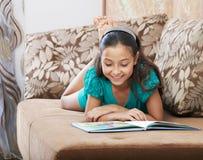 A menina de encontro está lendo o magasine Fotografia de Stock Royalty Free
