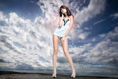 Menina de encontro a um céu nebuloso Fotografia de Stock Royalty Free