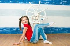 Menina de encontro a uma roda de direcção do navio Fotos de Stock Royalty Free