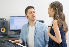 Menina de ensino do treinador vocal masculino como cantar fotos de stock