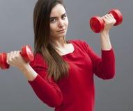 Menina de escritório 20s focalizada que guarda sinos mudos para os braços tonificados e o bem estar Imagens de Stock