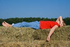 Menina de exploração agrícola de sono que coloca nas balas da palha. Foto de Stock