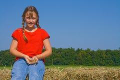 Menina de exploração agrícola feliz pronta para jogar a palha. Foto de Stock