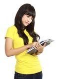 Menina de faculdade asiática que lê um livro fotografia de stock royalty free