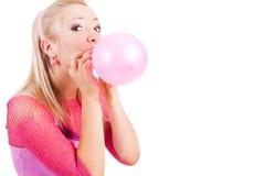 A menina de fascínio nova infla um balão Fotos de Stock