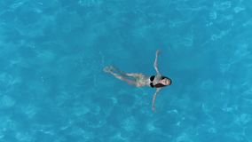 Menina de flutuação na associação com água claro que aprecia férias de verão, vista aérea filme