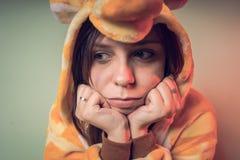 Menina de Garus que está contra a parede nos pijamas e olhares pensativamente ao lado foto de stock