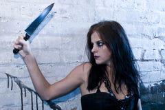 Menina de Goth que prende uma faca imagem de stock