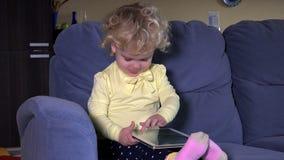 A menina de grito da criança pequena obtém o tablet pc e acalma-se para baixo imediatamente vídeos de arquivo