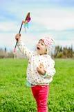 Menina de Hapy com moinho de vento fotografia de stock