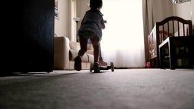 A menina de Hapy monta no 'trotinette' cor-de-rosa em casa video estoque
