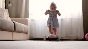 A menina de Hapy monta no 'trotinette' cor-de-rosa em casa filme