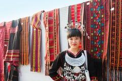 A menina de Hmong em seu vestido tradicional está vendendo vestuários e lenço de Hmong imagens de stock