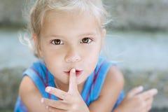 A menina de Ittle põr seu dedo para mouth fotografia de stock royalty free