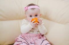 Menina de Ittle que come a laranja Fotos de Stock