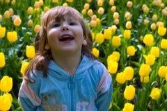 Menina de Laughting nos tulips Fotografia de Stock Royalty Free