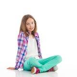 Menina de Liitle que senta-se com os pés cruzados Imagens de Stock
