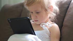 Menina de Litlle que joga com tabuleta vídeos de arquivo