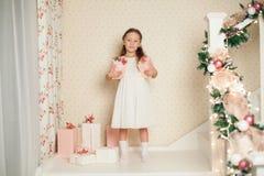 Menina de Littile no vestido com presentes do Natal imagem de stock