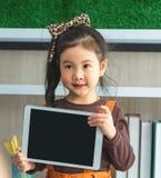 Menina de Littlg que guarda a zombaria vazia da tabuleta acima na sala de aula imagem de stock royalty free