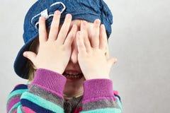 A menina de Llittle cobre a cara com suas mãos Imagem de Stock Royalty Free
