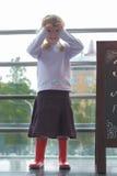 Menina de Llittle com seus dedos em torno de seus olhos Imagens de Stock Royalty Free