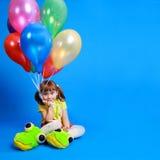 Menina de Llittle que prende balões coloridos Fotografia de Stock Royalty Free