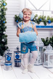 Menina de LSmiling que está ao lado de uma árvore e de um Cristo de Natal foto de stock