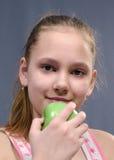 Menina de Lteen com a maçã verde em sua mão Imagens de Stock Royalty Free