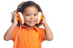 Menina de Lttle com um penteado afro que aprecia sua música em fones de ouvido alaranjados brilhantes foto de stock royalty free