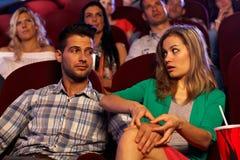 Menina de molestamento do homem novo no cinema na primeira data Imagem de Stock