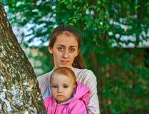 Menina de olhos azuis com sua mãe nova exterior Imagens de Stock Royalty Free