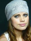 Menina de olhos azuis em um tampão cinzento com pastas Imagem de Stock