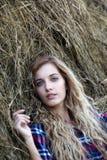 Menina de olhos azuis loura nova do país perto dos monte de feno Imagens de Stock Royalty Free