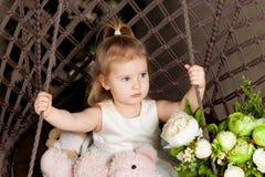 A menina de olhos azuis loura pequena que senta-se em uma malha do balanço Fotos de Stock