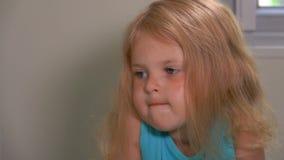 A menina de olhos azuis pequena bonito é triste e morde seus bordos video estoque