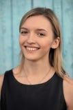 Menina de olhos castanhos loura de sorriso nova no vestido preto contra o azul Imagem de Stock