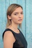 Menina de olhos castanhos loura tímida nova com cabelo reto longo no blac Foto de Stock Royalty Free