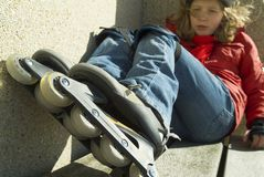 Menina de patinagem que senta-se em um banco imagens de stock royalty free