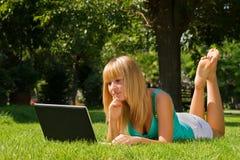 Menina de pensamento nova na grama com caderno Imagens de Stock