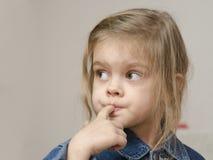 A menina de quatro anos com um dedo no olhar da boca saiu Fotos de Stock