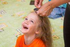 Menina de quatro anos de assento velho e riso felizmente, quando fez seu cabelo Fotografia de Stock Royalty Free