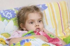 A menina de quatro anos está na cama sob a cobertura Imagens de Stock