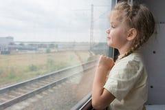 A menina de quatro anos olha para fora a janela do carro de trem foto de stock